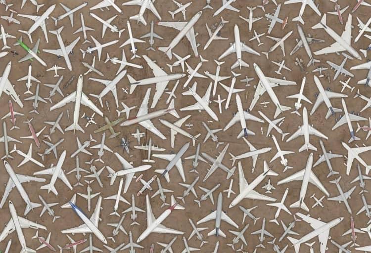 dezenas de aviões no deserto, apontando para várias direções e vistos de cima, apontando para o norte, sugerindo formas geométricas