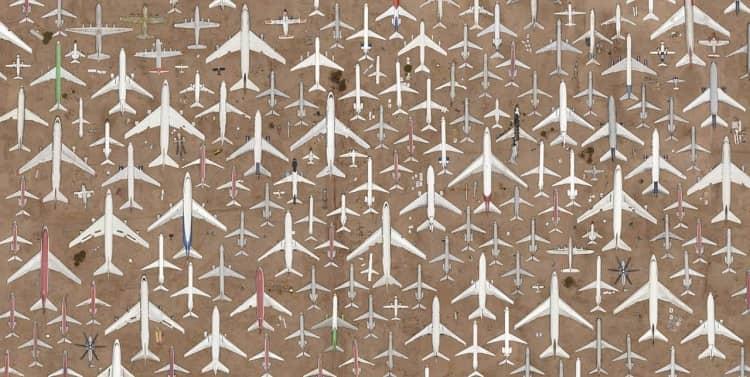 dezenas de aviões no deserto, vistos de cima, apontando para o norte, sugerindo formas geométricas