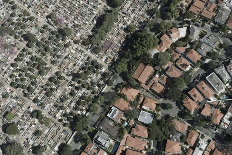 Vistos do alto, muito longe, separados por uma linha diagonal da esquerda baixo para direita no alto: cemitério e casas
