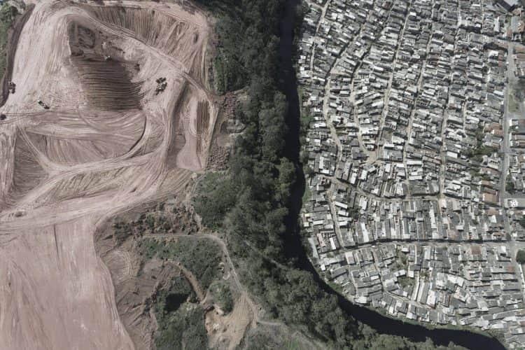 Campo separado de uma favela por um rio