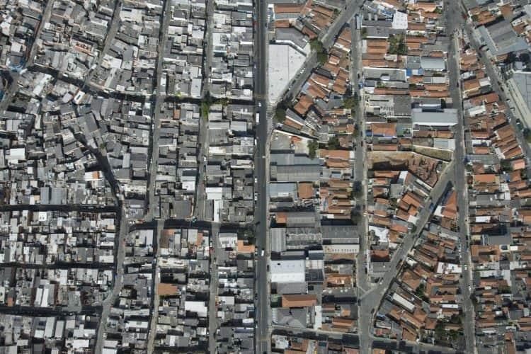 Vistos do alto, muito longe: favela na esquerda e bairro de classe média na direita