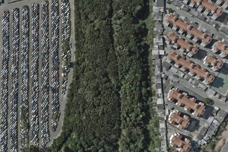 Vistos do alto, pátea de carros, mata e condomínio fechado